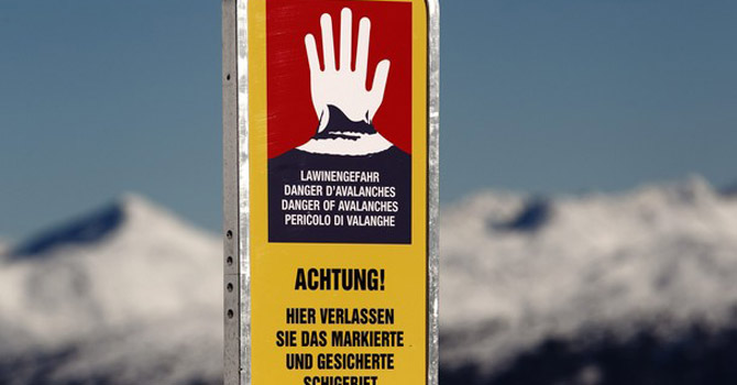 "An avalanche warning sign that reads ""You are leaving the marked and secured area - alpine dangers"" is placed on a mountain.—Reuters Photo"