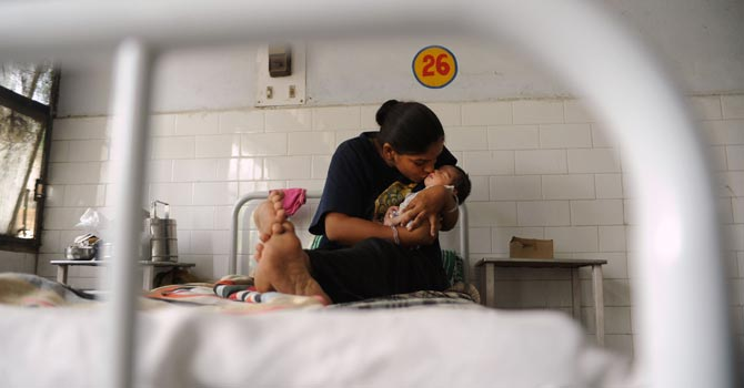An Indian mother kissing her new born daughter in a maternity ward at a public hospital in Nawanshahr. — AFP Photo