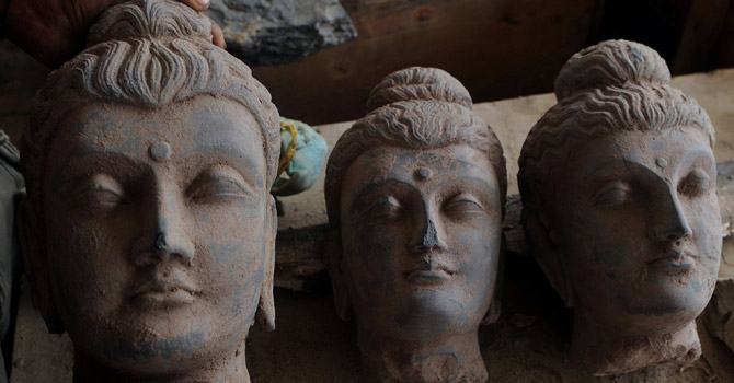 A man arranges seized ancient statues in a police station in Karachi.—AFP Photo