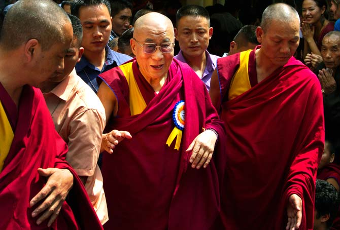 Tibetan spiritual leader the Dalai Lama, centre, is escorted by Tibetan monks as he leaves Tsuglakhang temple in Dharmsala. ? Photo by AP