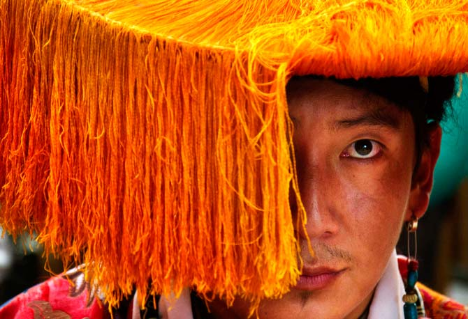 An exile Tibetan in traditional costume waits to perform a dance at Tsuglakhang temple. ? Photo by AP