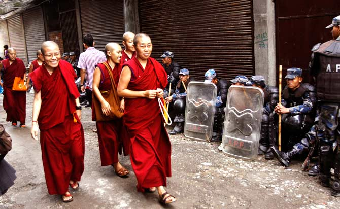 Tibetan nuns arrive at Chusang monastery as Nepalese police officers guard in Katmandu. ? Photo by AP