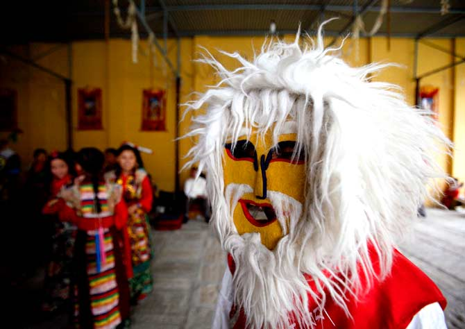 A masked dancer with gets ready to perform a mask dance. ? Photo by Reuters