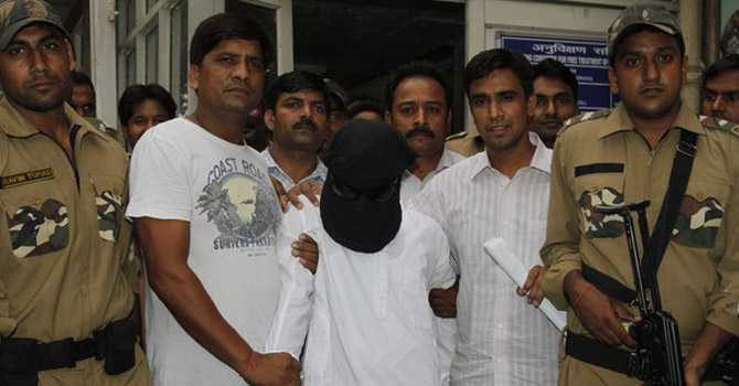 Delhi police officers escort Syed Zabiuddin Ansari.—AP Photo