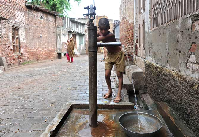 A boy draws water through a hand pump near the house of Professor Abdus Salam.