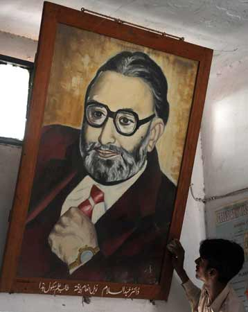 A worker cleans the portrait of Professor Abdus Salam at the state-run school where he received his early education.