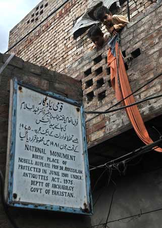 Boys look at a signboard hangs outside the house of Professor Abdus Salam in the town of Jhang.