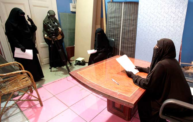 A program is filmed in a studio of a new TV channel which is being managed and run exclusively by women who wear the full veil, to be launched this weekend, in Cairo on the first day of Ramazan. ? Photo by Reuters