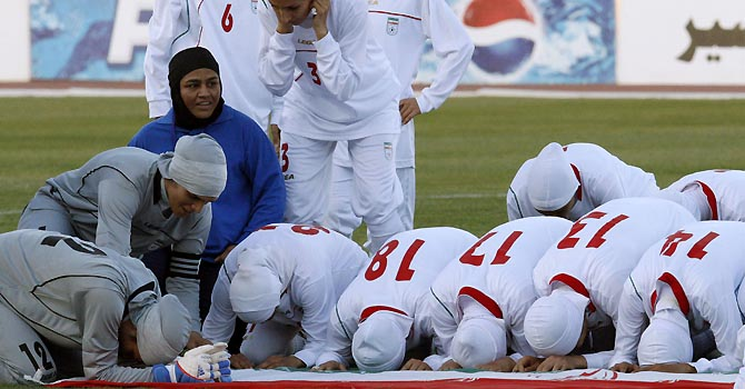 A picture dated June 3, 2011 shows players of the Iranian national women football team kneeling around their national flag in Amman, moments after they were barred from playing an Olympic qualifier against Jordan for wearing the traditional Islamic headscarf. The football governing board FIFA announced on July 5, 2012 their decision to authorize the wearing of headscarves by female players in FIFA competitions.  AFP PHOTO/STR