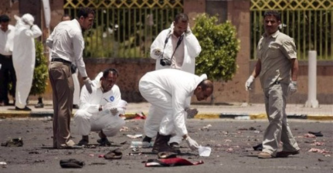 Forensic policemen collect evidence at the site of a suicide bomb attack.—AP Photo