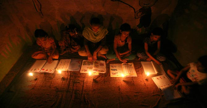 Girls study in the light of candles inside a school during power-cut in Noida on the outskirts of New Delhi. — Reuters Photo