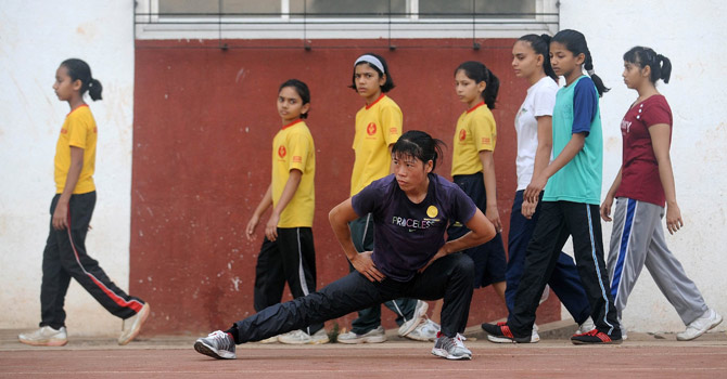 Indian boxer MC Mary Kom (C) warms up during a training session for the 2012 London Olympics.—APF Photo
