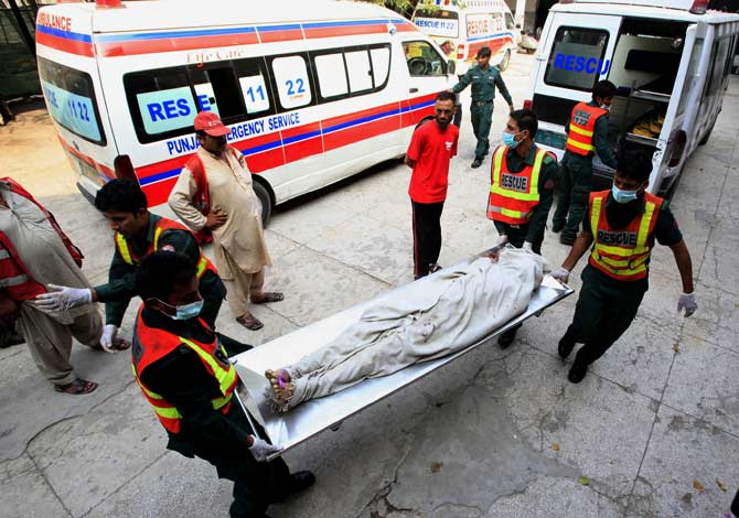Rescue officials carry a body to a hospital. ? Photo by AFP