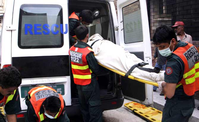 Rescue officials carry a dead body after an attack on police hostel.? Photo by AFP