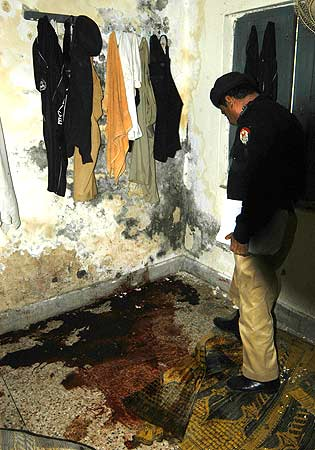 A Pakistani police officer inspects  the attack site at the police hostel. ? Photo by AFP