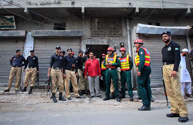 Policemen and rescue workers gather outside a building where unidentified gunmen killed police cadets. ? Photo by Reuters