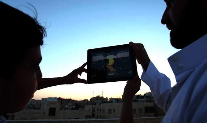 Majd Osama, 13, shows his father, Osama Shawqi, 41, the crescent moon's course in the sky through an application on his iPad in order to try to locate the crescent of Ramazan in Amman,  Jordan. ? Photo by AP
