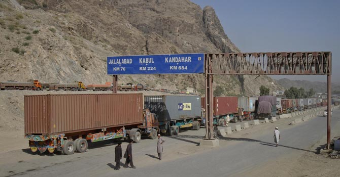 Men walk near a road sign showing the distance to cities in Afghanistan, as trucks drive past in the northwest town of Torkham, at the border crossing to Pakistan, July 4, 2012. Pakistan and the U.S. reached a deal on Tuesday to reopen land routes that the North Atlantic Treaty Organization (NATO) uses to supply troops in Afghanistan, ending a seven-month crisis that damaged ties between the two countries and complicated the U.S.-led Afghan war effort.