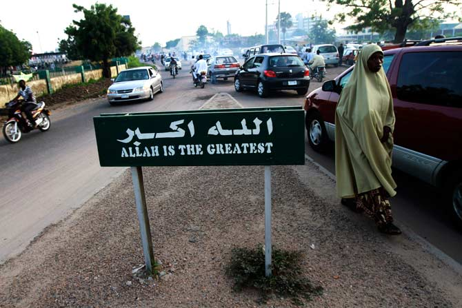 A woman walks past a signboard on a road, a day before the start of the holy month of Ramadan, in Nigeria's northern city of Kano. ? Photo by Reuters