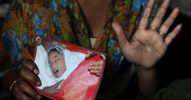 The mother of an 11-year-old girl who died in a New Delhi children's home in December 2011 and was later found to have been sexually abused, holding a picture of her daughter.—AFP Photo