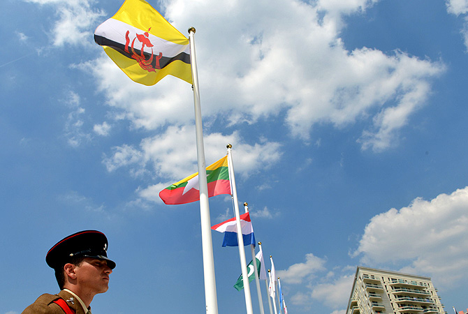 Flags of Brunei (L), Myanmar (2nd L), Netherlands (3rd L) and Pakistan (4th L) flutter during the flag raising ceremony at the Olympic village.
