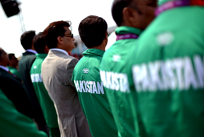 Pakistani athletes listen to the Olympic anthem.