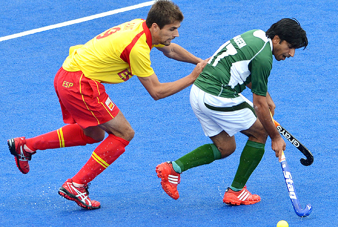 Spain's national hockey team's forward Pablo Amat (L)  is tackled by Pakistan's hockey team's midfielder Waseem Ahmad. -Photo by AFP