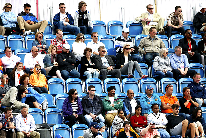 Spectators watch the men's Group A hockey match between Spain and Pakistan. -Photo by Reuters
