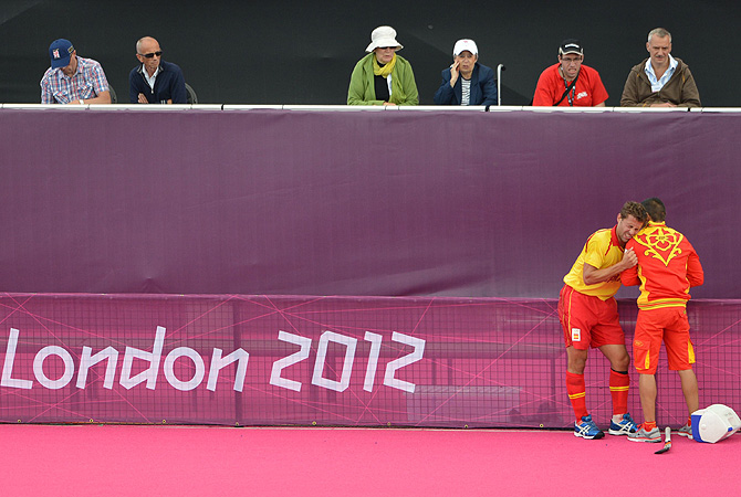 Spectators look on as Spain's forward Santiago Freixa gestures in pain after getting injured. -Photo by AFP