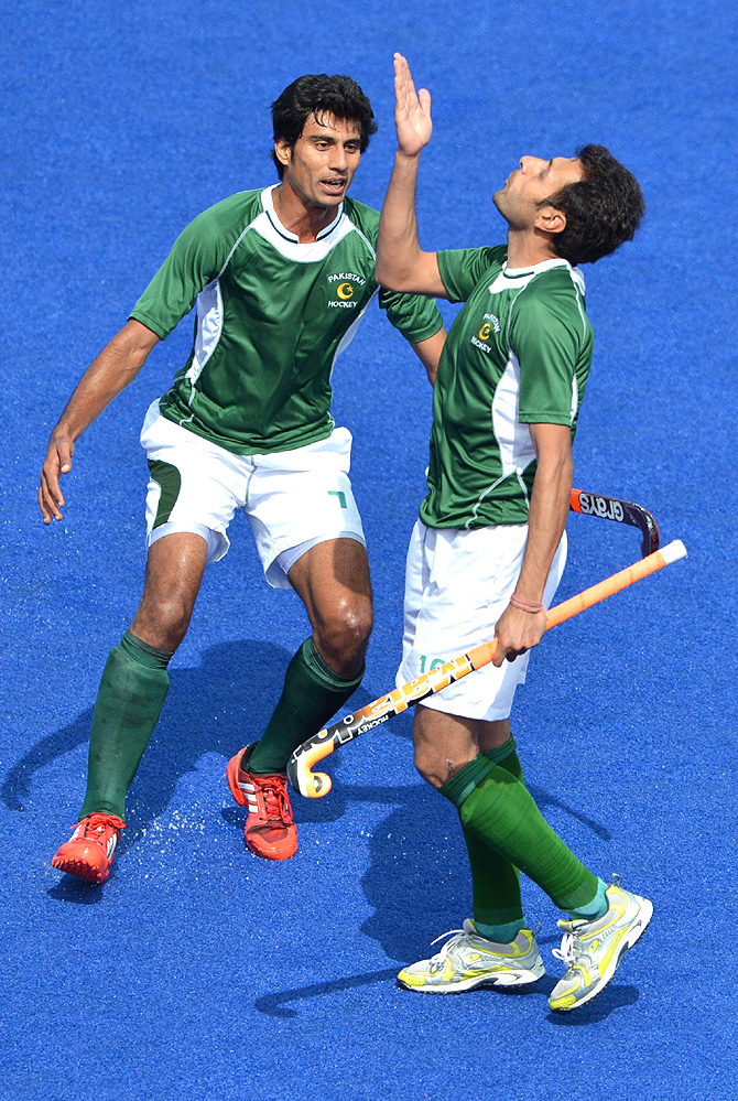 Pakistan's forward Rehan Butt (R) celebrates after scoring a goal as teammate Muhammad Waqas runs to congratulate him. -Photo by AFP