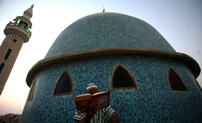 A Palestinian reads from the Quran during the dawn prayer on the first day of Ramazan at a mosque in the West Bank city of Jenin. ? Photo by AP