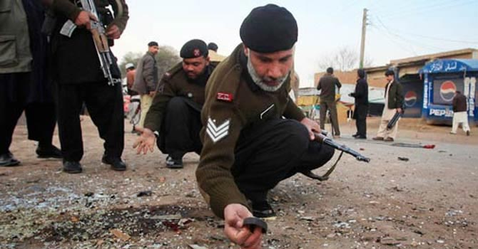Pakistani policemen investigating on the crime scene.—File Photo