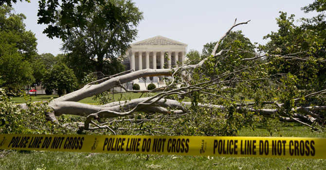 An American beech tree is down on Capitol Hill grounds in Washington Saturday, June 30, 2012 across theU.S. Supreme Court, background, after a powerful storm swept across the Washington region late Friday.   Violent storms swept across the eastern U.S., killing at least nine people and knocking out power to hundreds of thousands on a day that temperatures across the region are expected to reach triple-digits.  (AP Photo/Manuel Balce Ceneta)