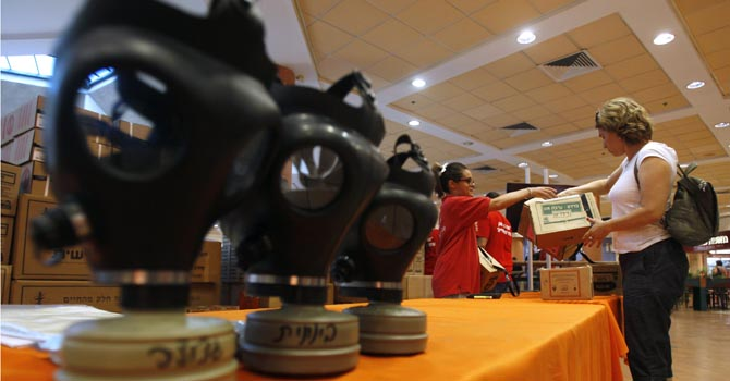 A woman receives a gas mask kit at a distribution point in a shopping mall in Mevasseret Zion, near Jerusalem July 24, 2012.  The Syrian government is still in full control of its chemical weapons stockpiles, Israeli defence officials said on Tuesday, in an apparent bid to calm fears that a non-conventional conflict could be looming. But concern that the stockpiles could fall into the hands of Hezbollah, the Lebanese Islamist group, stoked demand in Israel for state-funded gas masks, which have been distributed over the past few years as part of the country's wider preparations for a possible showdown over arch-foe Iran's disputed nuclear programme. REUTERS/Baz Ratner (ISRAEL - Tags: POLITICS CONFLICT)
