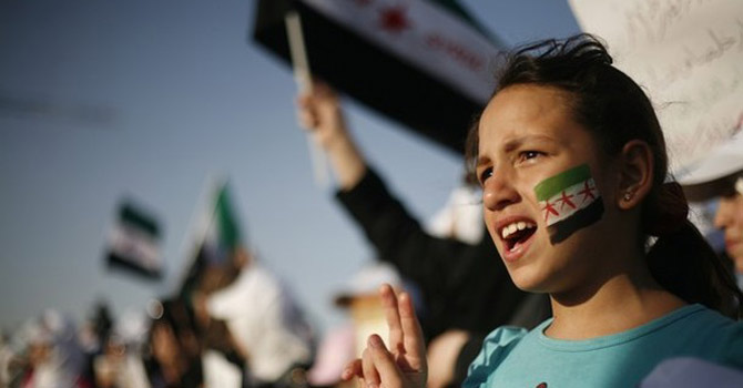 Syrian girl wears the colours of the revolutionary flag on her face.—AP Photo