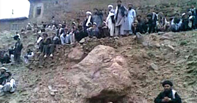 This frame grab received on July 8, 2012, taken from an undated video which was handed over by a Qol villager to the Parwan provincial government shows a gathering of people watching the execution by gunfire of a 22 year old woman named as Najiba (not pictured) in Qol village, Parwan province, north of Kabul. — Videograb provided by AFP