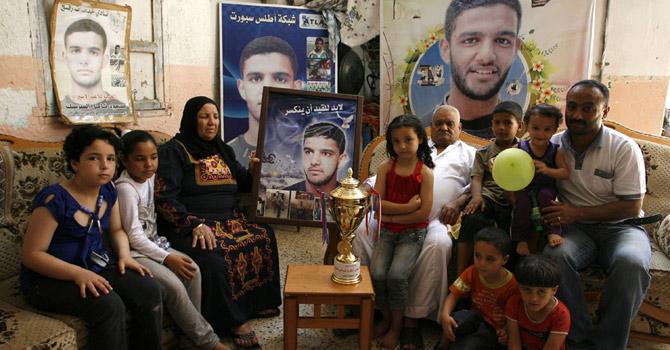 The family of Palestinian prisoner Mahmud Al-Sarsak, sits in front of his images at their home.- AFP Photo