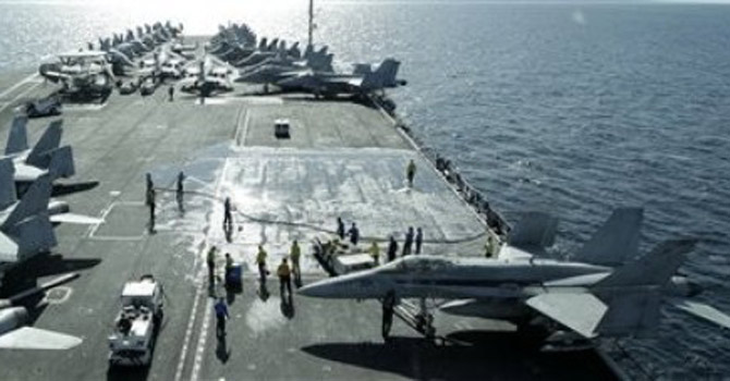 US aircraft jets parked on the flight deck in the Strait of Hormuz.—AP Photo