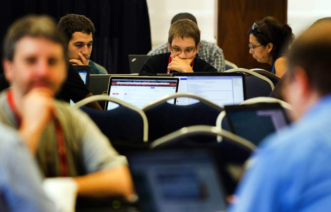 Computer hackers participate in the Wikimania Hackathon at George Washington University in Washington, DC. – Photo by AFP