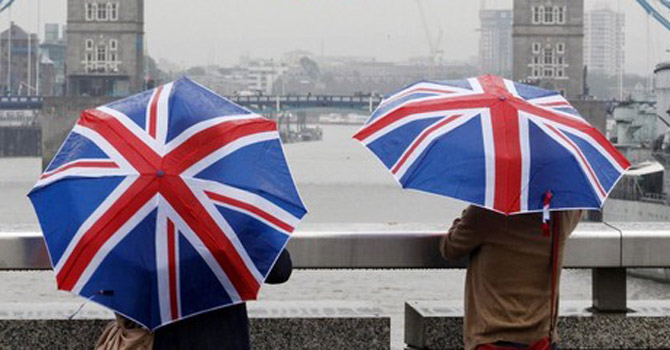 People standing under Union flag umbrellas.—Reuters Photo