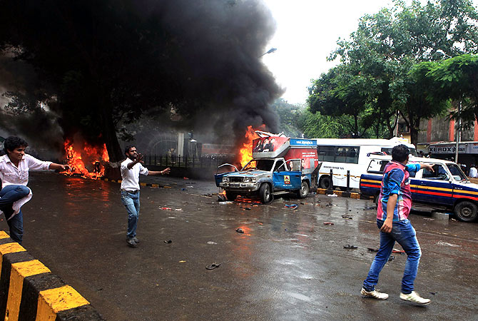 Vehicles set on fire by demonstrators burn outside the Azad Maidan ground area in Mumbai. -Photo by AFP