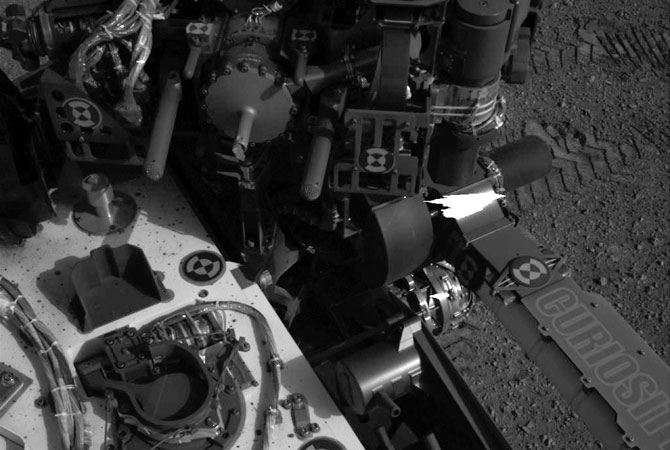 This image released by NASA shows tracks (Upper-R) made by Curiosity's tires during its first test drive as seen by Navcam: Left A (NAV_LEFT_A) on board NASA's Mars rover Curiosity on Sol 16, August 22, 2012.