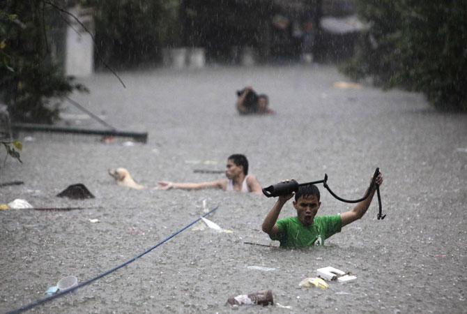 Men crosses deep floodwaters in San Juan, north of Manila, Philippines. Widespread flooding paralyzed the Philippine capital and many other areas on Wednesday as rescue efforts focused on the large number of distressed residents who are still marooned on their roof tops and unable to move to high ground. ? Photo by AP