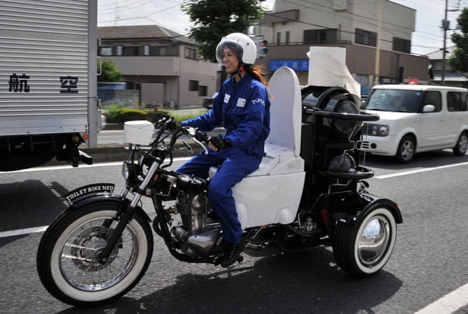 A female rider drives Japanese toiletry goods maker Toto's eco-friendly motorcycle ?Toilet Bike Neo?, which uses bio-gas from discharges of livestock or waste water during a demonstration run for their domestic green campaign in Omiya, suburban Tokyo on August 29, 2012.
