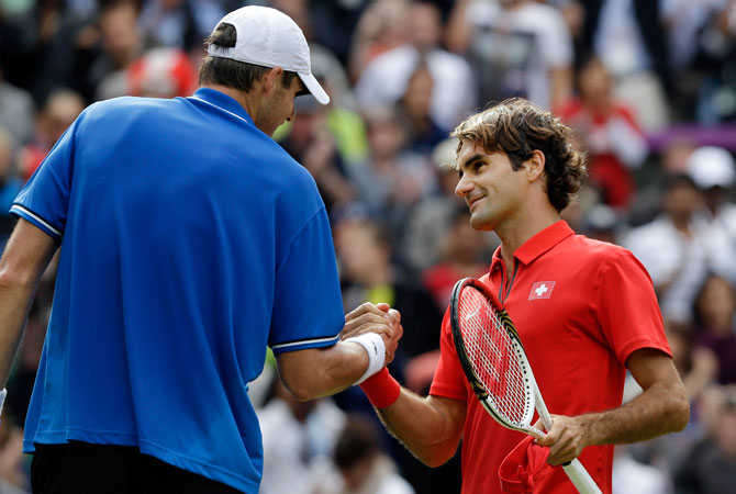 Roger Federer, right, of Switzerland shakes hands after defeating John Isner of the United States at the All England Lawn Tennis Club in Wimbledon, London at the 2012 Summer Olympics, Thursday, Aug. 2, 2012. ? Photo by AP