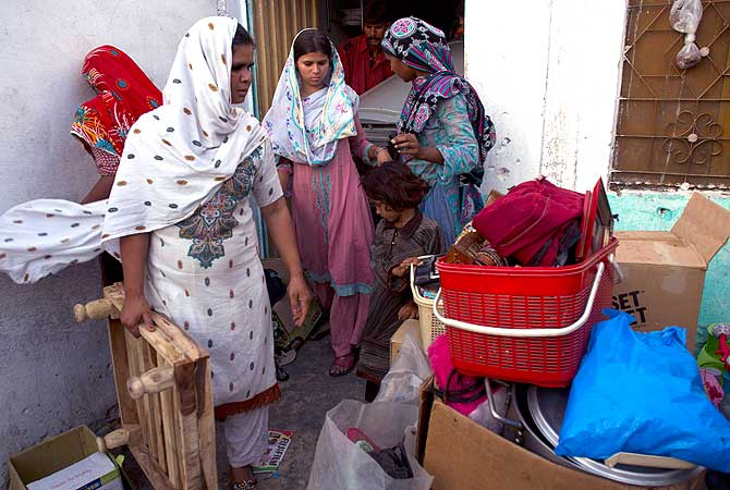 Pakistani Christian women collect their belongings to leave their home in a suburb of Islamabad, Pakistan on Thursday, Aug. 23, 2012. — AP Photo