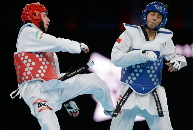Turkey's Servet Tazegul fights Iran's Mohammad Bagheri Motamed (in red) during their gold medal match in men's 68-kg taekwondo competition at the 2012 Summer Olympics, Thursday, Aug. 9, 2012, in London.