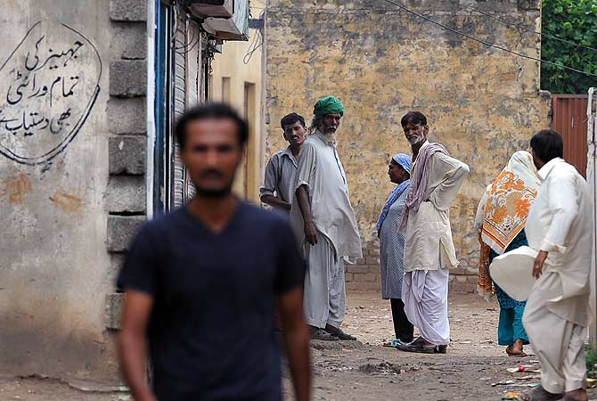 Pakistani Muslims look on in the low-income neighbourhood of Mehrabad in the suburb of the capital Islamabad. — AFP Photo