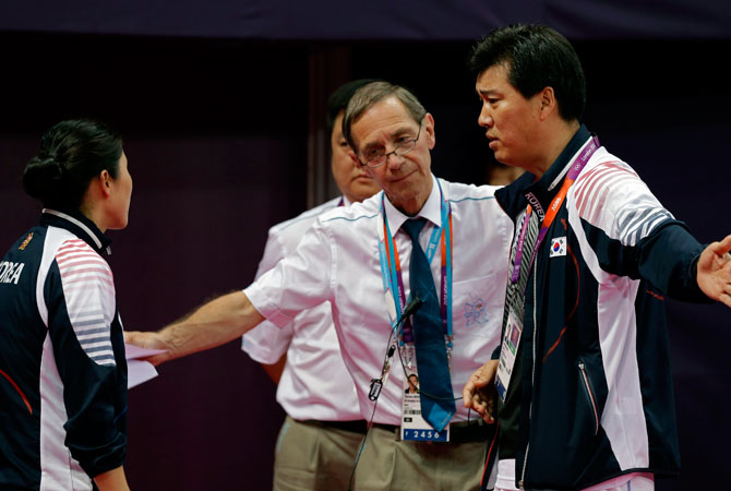 Head badminton referee Torsten Berg, second from right, talks to South Korea's head badminton coach Sung Han-kook, right, after Berg issued a black card to the players in the women's doubles badminton match between South Korea's Ha Jung-eun and Kim Min-jung, and Indonesia's Meiliana Jauhari and Greysia Polii at the 2012 Summer Olympics, Tuesday, July 31, 2012, in London. At left is an unidentified South Korean coach. ? Photo by AP