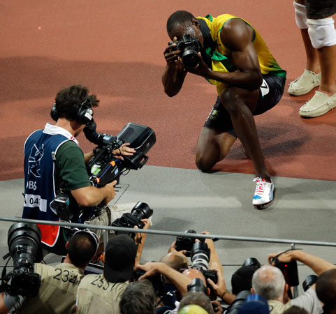 Jamaica's Usain Bolt uses a photographers camera as he takes pictures after winning the gold medal in the men's 200-meter during the 2012 Summer Olympics, Thursday, Aug. 9, 2012, in London.